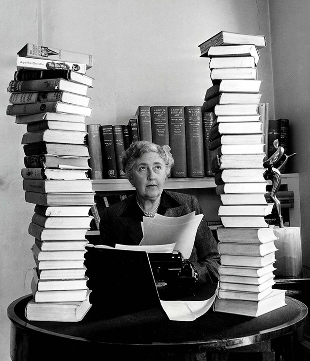 Agatha Christie behind her desk with towers of her own books