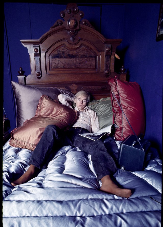 Andy Warhol on the bed of his home in New York